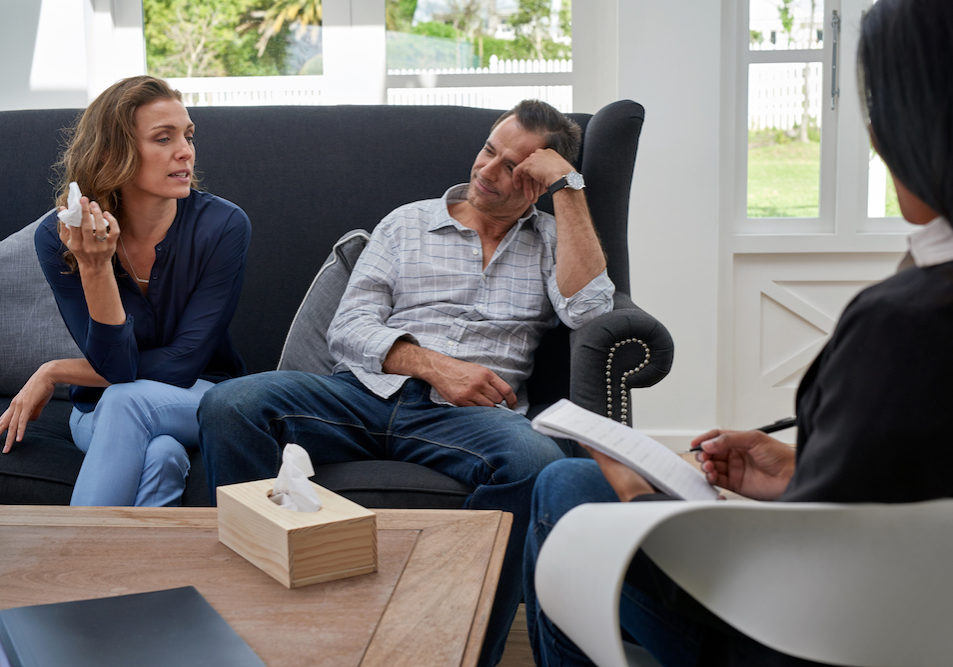 mature couple seated on couch, woman crying during therapy session